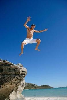 Man jumping off rocks