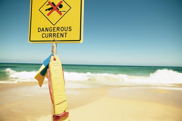 Detail view of a 'Dangerous Current' sign in front of breaking waves