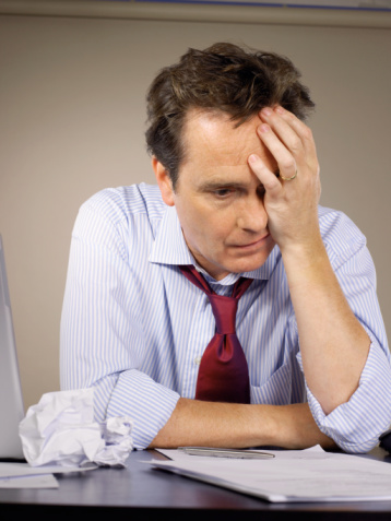 Businessman sitting at desk holding head in hand